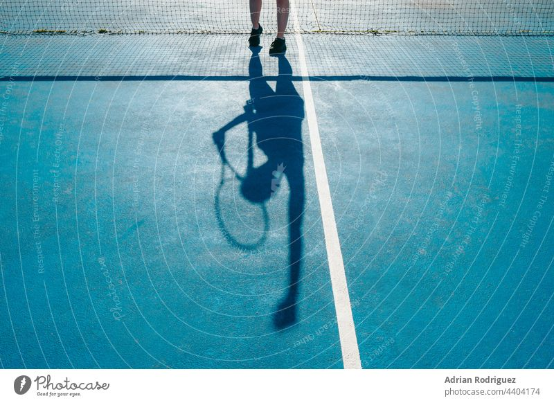 A woman's shadow while serving a tennis ball on a court. racket sport competition game courtyard ground stadium athlete web tournament exercise field alone