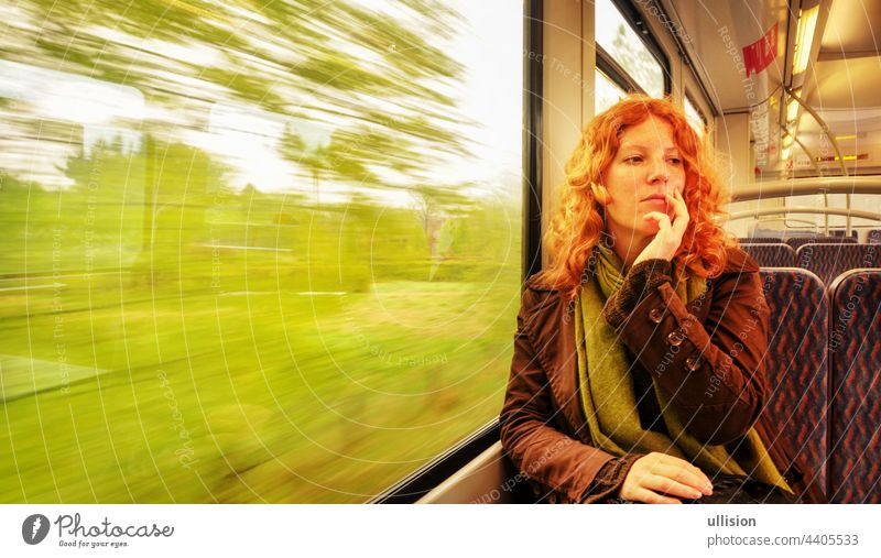 Young red-haired beautiful sexy woman sitting daydreaming daydreaming in a moving commuter train with copy space Copy Space Daydreaming Woman Sitting