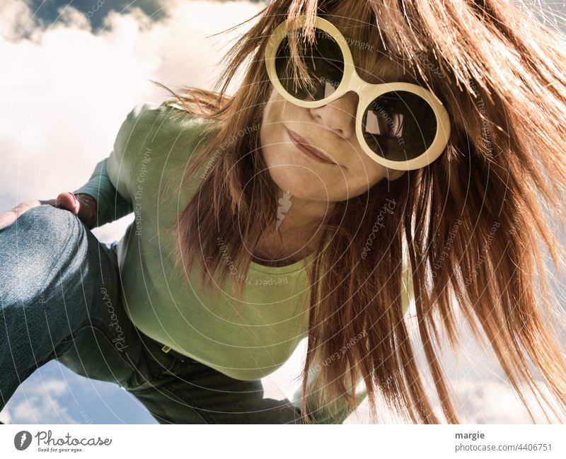 A woman with big sunglasses looks into the photo camera Woman Eyeglasses blonde hair Face Young woman Hair and hairstyles portrait Feminine sexy pretty