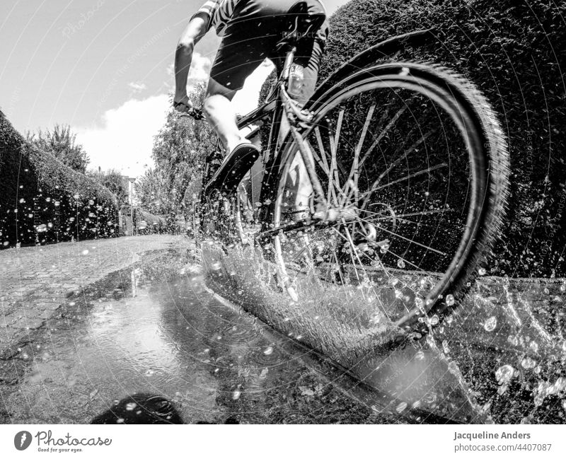 Cyclist rides through a puddle activity blurriness Summer Leisure and hobbies Gray Lanes & trails Weather Exterior shot people Transport Healthy muck about