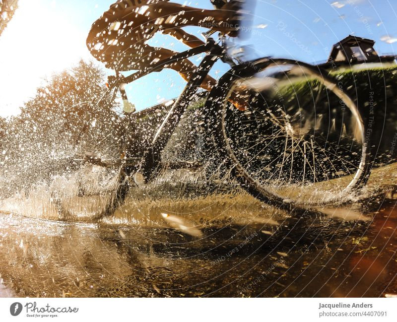 Cyclist rides through a puddle in summer Bicycle Cycling cyclist Puddle reflection Inject Water Sports Street Transport Movement cyclists Outdoors Lifestyle