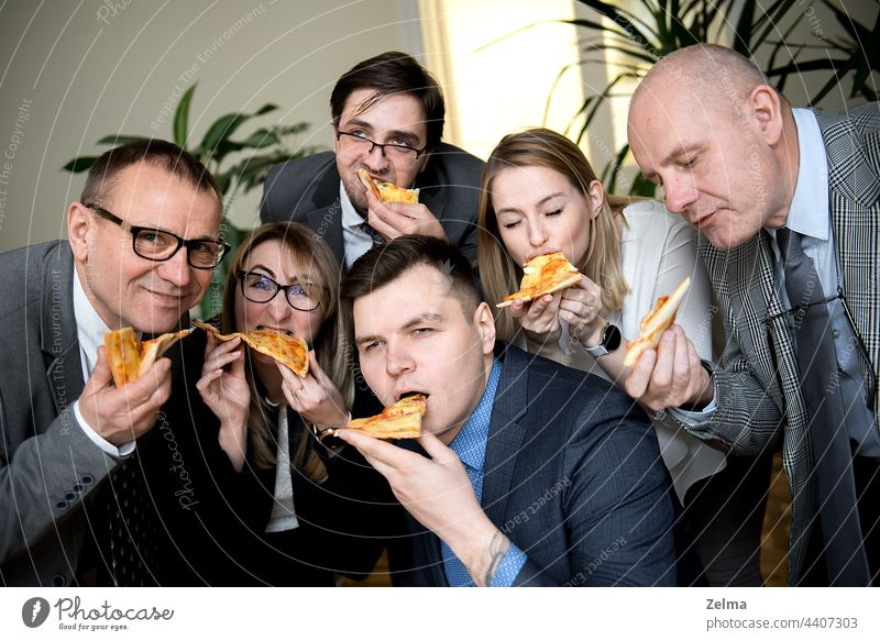 business, food, lunch and people concept - happy business team eating pizza in office finance friends sharing group meal businessmen businesswomen cheerful