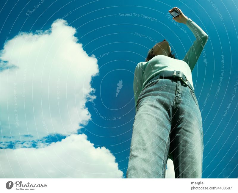 Sky, clouds, a woman searches for the connection in her smartphone, mobile phone Clouds Blue sky Sun Beautiful weather Woman mobile phone photo Sunlight Jeans