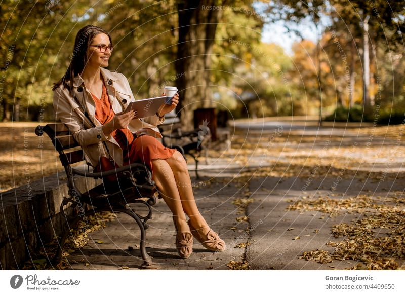 Young woman drinks coffee and using digital tablet in the park alone attractive autumn bench caucasian device forest internet laptop leaves leisure lifestyle
