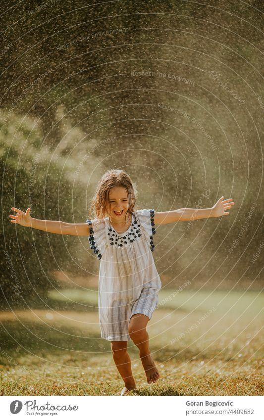 Cute little girl having fun under irrigation sprinkler happy kid summer happiness joy spray wet active water outdoor splash child activity young freedom leisure