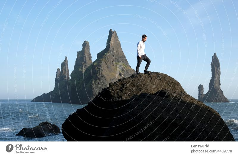 Man standing on a rock at Reynisfjara Black Beach, Iceland, with wind in his hair adventure black beach blue cliff concept freedom handsome hiking hill iceland