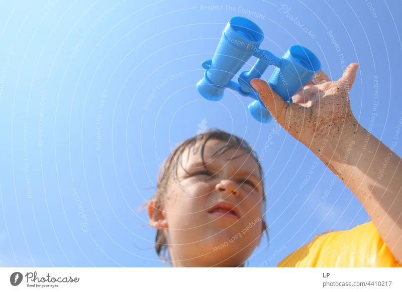 child looking through a toy binoculars outdoors looking away observe positive shore freedom vacation seaside enjoying carefree childhood casual cute day
