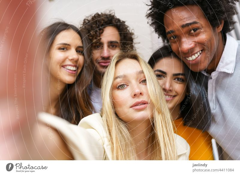 Multi-ethnic group of friends taking a selfie together while having fun outdoors. people smartphone multiracial multi-ethnic russian blonde girl caucasian