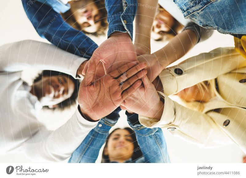 Hands of a multi-ethnic group of friends joined together as a sign of support and teamwork. hand people woman friendship students young partnership youth