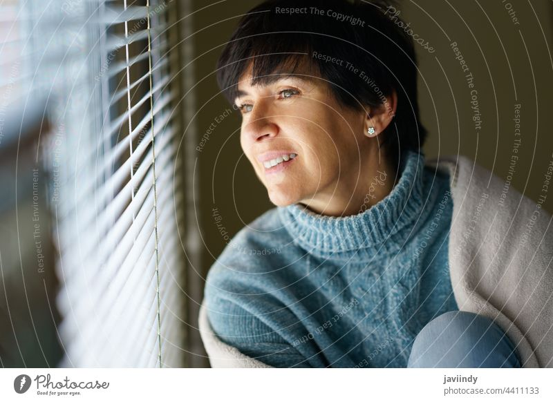 Happy middle-aged woman smiling while looking out the window. home 50s 40s female person brunette people interior smile relax white comfort indoor sweater