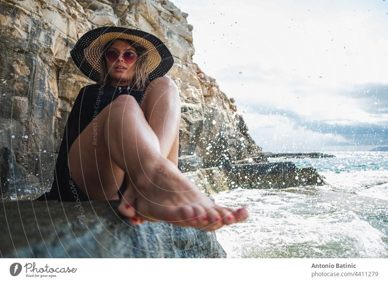 Attractive girl wearing a black dress, sunglasses and a hay hat sitting by the sea. Stormy day by the beach in Croatia, warm summer of 2021. Barefoot feet in foreground