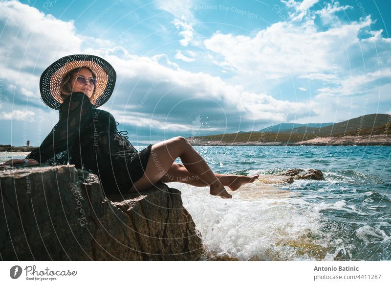 Amazing view of a brunette sitting on a rock near the sea. Amazing summer weather in Croatia , vis island. Sunbathing in the sun with waves hitting the shore