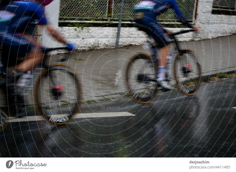 Two cyclists pedal full speed just before they reach a climb . They are both out of focus. Bicycle Cycling Street Transport Bikers Outdoors Sports Speed