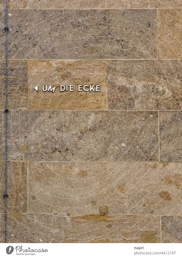 UM DIE ECKE... think | Silver letters retro-style on sandstone facade around the corner Clue Recommendation Information Orientation Road marking Navigation