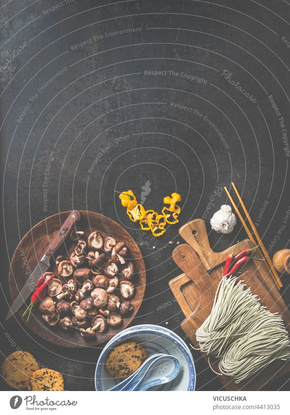 Delicious ingredients of Asian cuisine fresh made homemade noodles on cutting board and wooden plate with shiitake mushrooms, chili peppers, traditional soup bowls on a dark background. Frame.