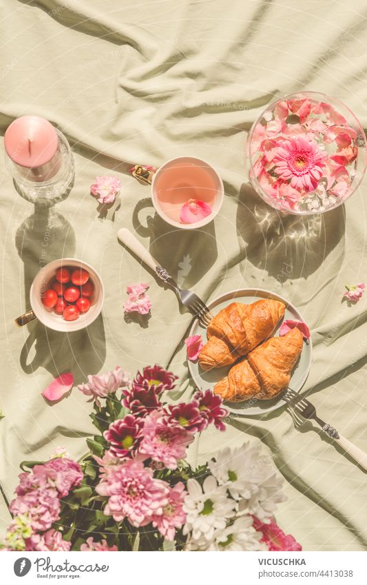 Sunny aesthetic picnic breakfast with flowers floating in crystal vases, croissants with tea from rose petals , bouquet of flowers and candles on blanket. Top view. Outdoor