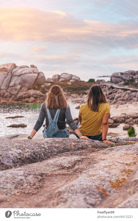 Two female friends contemplating the ocean copy space contemplation sunset oceanside rocks coastline mediterranean caucasian friendship sea vacation young woman