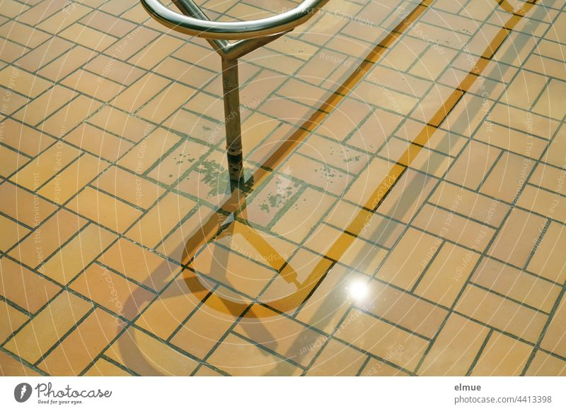 Partial view of a beige tiled Kneipp pool with metal handrail in the sunshine / treading water Kneipp basin Water Metabolic stimulation salubriously Metal