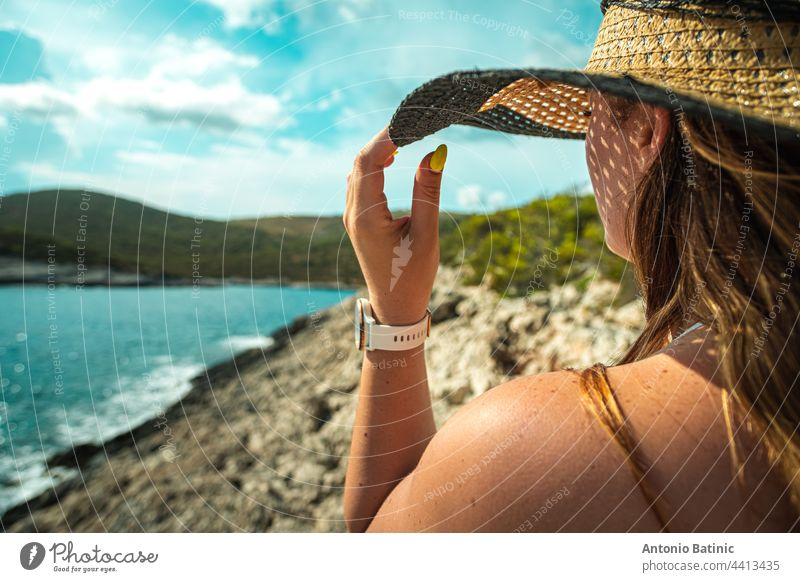Side view of an unrecognizable brunette girl, holding onto her hay hat in the summer. Standing near the shore of the adriatic sea, concepts of travelling, summer and vacations