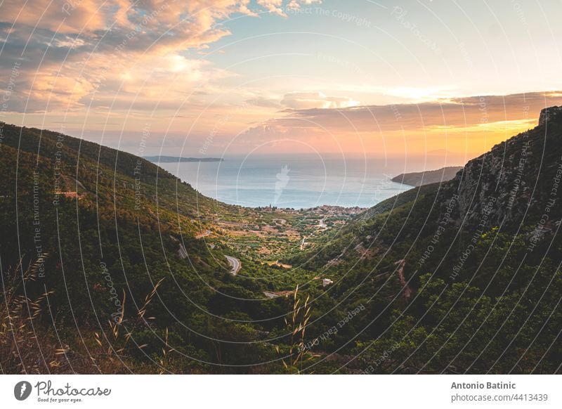 Amazing sunset on the Vis island in Croatia. Komiza city in the distance. Golden hour, orange sky and the beautiful blue adriatic sea. Green mountains surrounding the little picturesque town