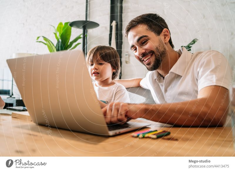 A father helping his son with online school at home. monoparental laptop homework student learning lifestyle quarantine family children people lock down indoor
