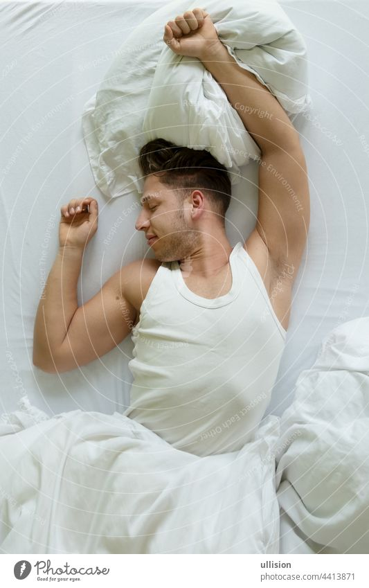 Bedtime. Top view of muscular young man in shirt stretches in bed in the morning, Copy space awake white comfortable fashion seducer sport valentine lover