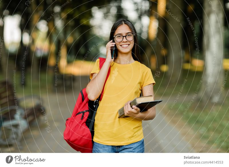 Portrait of a beautiful brunette with glasses and a backpack talking on the phone in the park girl student walking campus pretty books smiling holding young