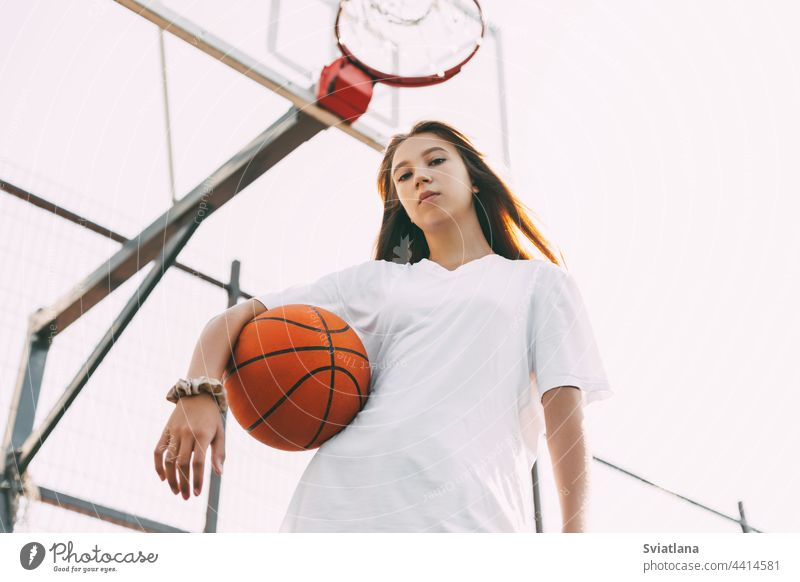 Portrait of young female basketball player. Beautiful teen girl playing basketball. in sportswear playing basketball teenager active woman caucasian portrait