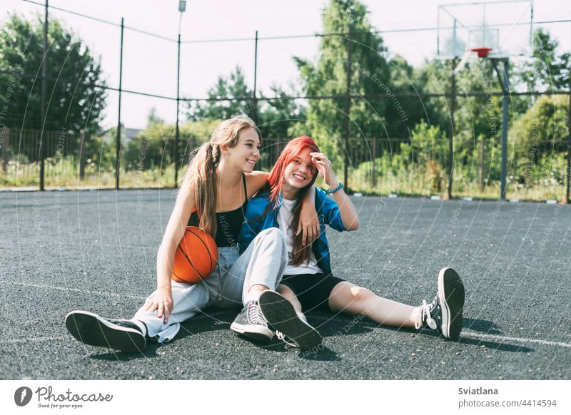 Two girls in sports clothes and with a basketball are chatting, sitting on the playground. Sports, competition, friendship teenager court team best friends