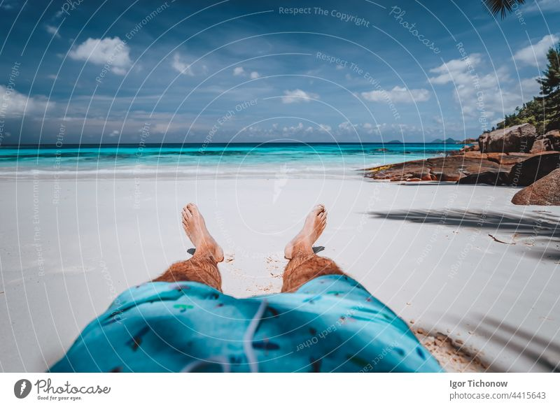 POV of male wearing swimming shorts with tanned legs on paradise white sand tropical exotic beach with view to turquoise blue ocean. Travel holidays vacation concept