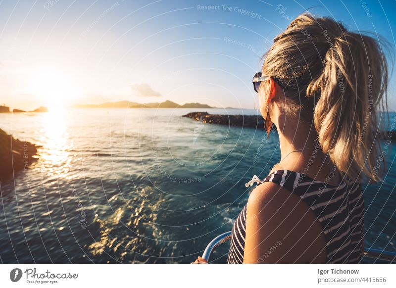 Young adult women enjoying sunset over ocean from ferry boat, Seychelles island, La Digue seychelles golden silhouette girl digue young travel summer vacation