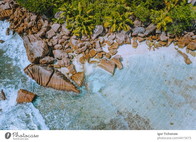 Seychelles. Aerial view of tropical paradise like beach Anse Cocos at La Digue Island with clear turquoise ocean and surreal granite rocks aerial sea white