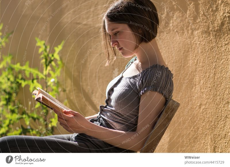 With a good book, the young woman can forget the time, especially on a sunny evening Reading Reader Book reading Girl Young woman hollowed grin submerged Forget