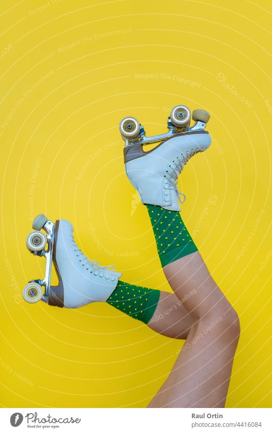 Woman with vintage quad roller skates and green socks on yellow background woman fun blade legs sport summer female lifestyle fashion boot skater foot fitness