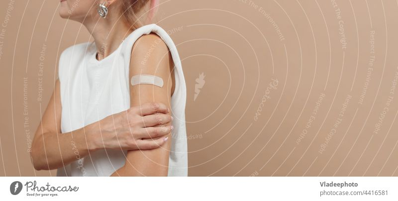Young hipster woman with band aid after coronavirus Covid-19 vaccine injection. Covid vaccination concept, plain color background covid arm young showing