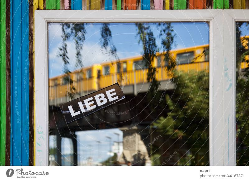 BerlinLIEBE | Window pane with large sticker LIEBE and the reflection of a passing subway train Kreuzberg Love Underground variegated Summer colourful City life