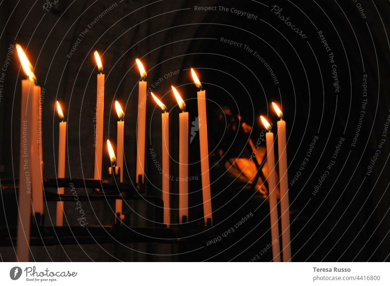 Burning candles illuminate a figure in the darkness shoulder stand Candlelight candlelight Illuminate Light Candle flame Flame Fire