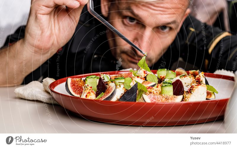 People at work. The chef prepares an tasty summer salad with ripe figs, goat chevre cheese, fresh cucumber roll, beetroot and mustard leaves with tomato sauce. Restaurant dish. Food banner
