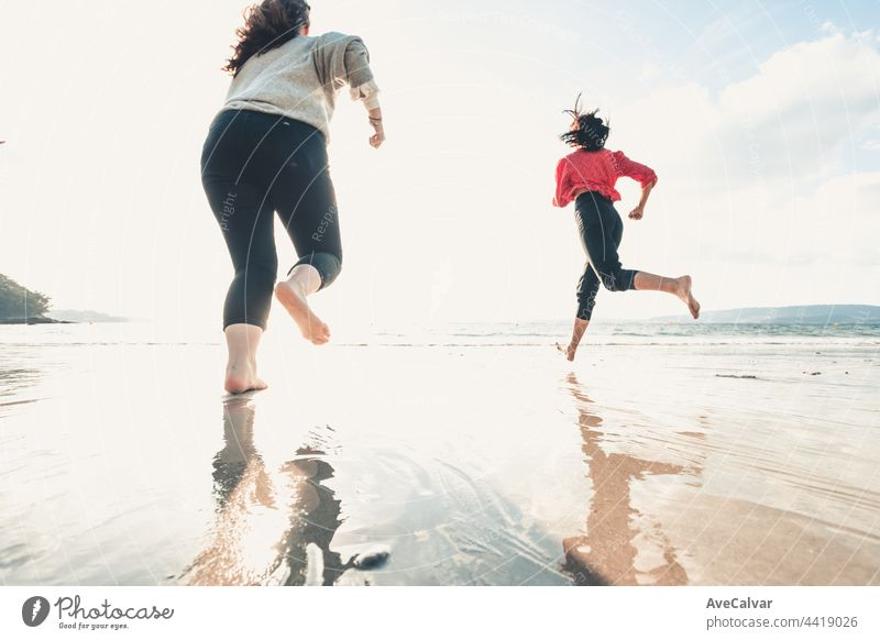 Happy women friends runs at sea beach during a bright day, friends happy relax having fun playing on beach near sea when sunset in evening. friendship party