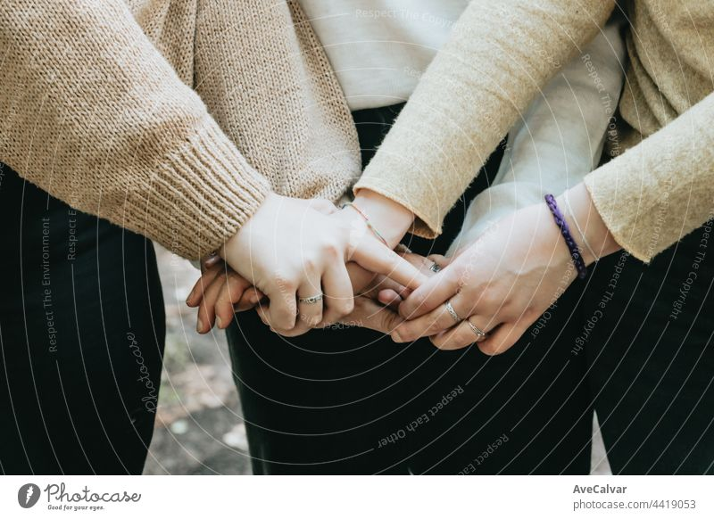 Hand of 3 persons touching together, friendship care and love concepts, copy space holding hands support togetherness happiness agreement meeting cooperation