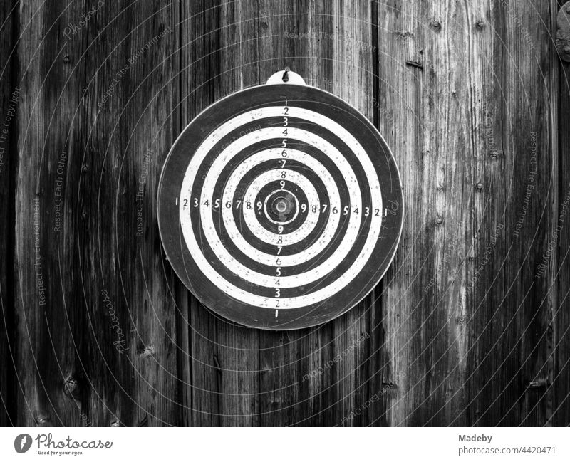 Circular old dartboard on a barn wall made of rustic wood on a farm in Rudersau near Rottenbuch in the district of Weiheim-Schongau in Upper Bavaria, photographed in classic black and white