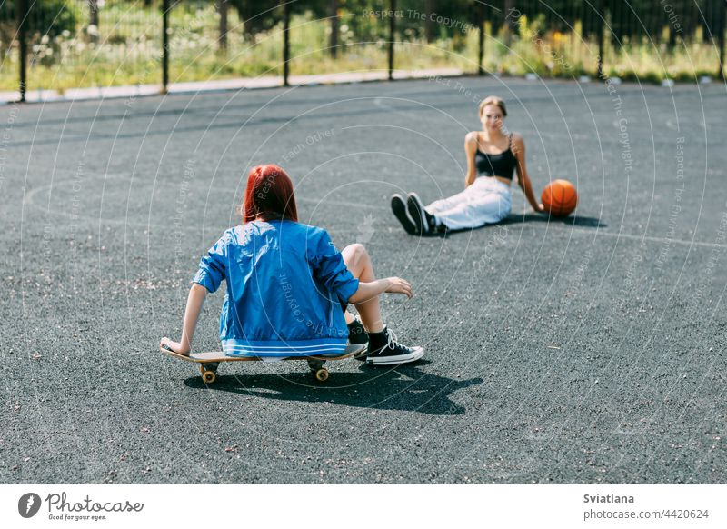 A young girl is sitting on a skateboard outdoors on a basketball court with her basketball player friend skateboarder sport skateboarding skating teenage ride