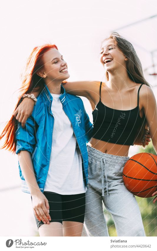 Two funny girls with a basketball hug each other after a game or workout. The concept of sports and friendship court holding best friends basketball court