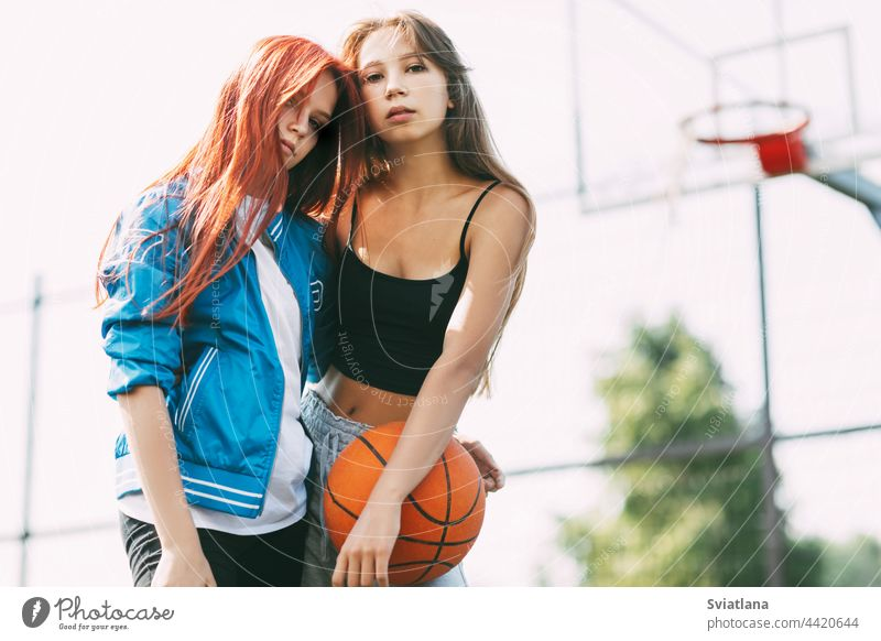 Portrait of two charming girls with a basketball on the sports field. Friendship, best friends, sports court holding friendship basketball court girlfriend