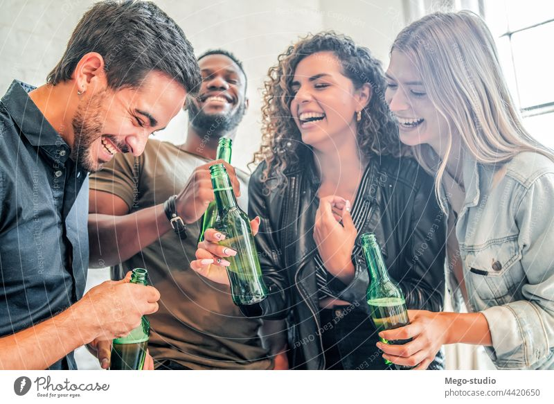 Friends having fun while drinking beer together. home group friends happy friendship party smile cheers female smiling happiness enjoy man woman indoors bottle