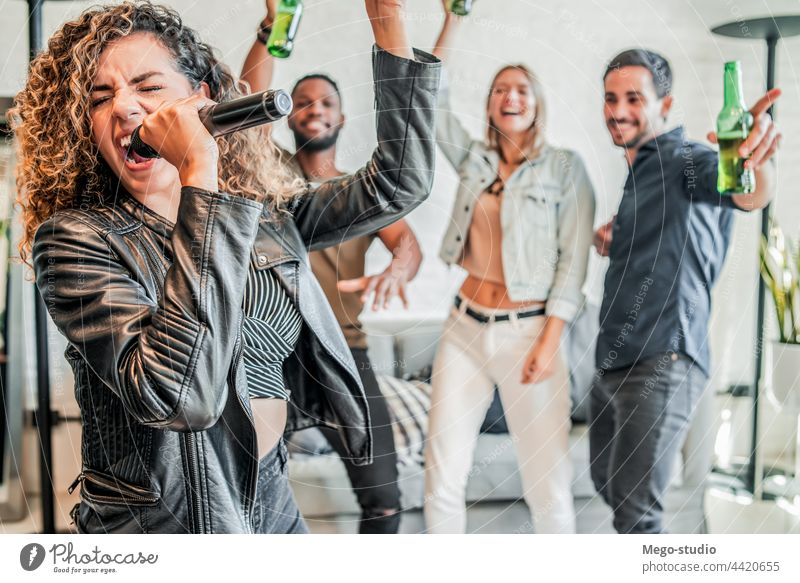 Group of friends playing karaoke at home. group together sing microphone entertainment friendship party lifestyle technology enjoyment happiness drink fun beer
