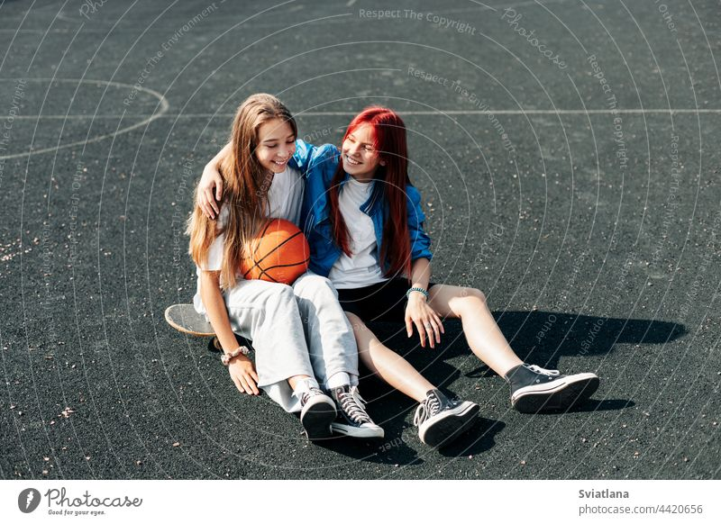 A couple of teenage girls on a sports street court with a basketball lifestyle relax after a game and talk. The concept of sports and a healthy lifestyle