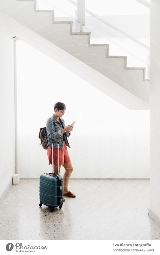 wide angle view of backpacker caucasian woman at train station using mobile phone app while waiting. Travel concept travel technology baggage internet online