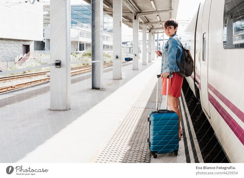 young backpacker caucasian woman holding luggage at train station ready to catch the train. Holding mobile phone while using app. Travel concept travel