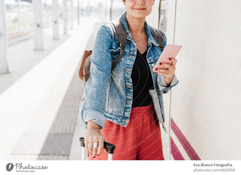 close up of backpacker caucasian woman holding luggage at train station ready to catch the train. Holding mobile phone while using app. Travel concept travel